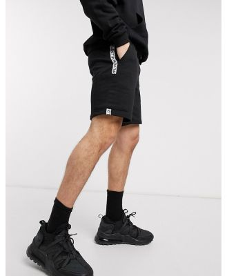 ASOS Unrvlld Supply relaxed shorts in black with side pockets and brand taping detail