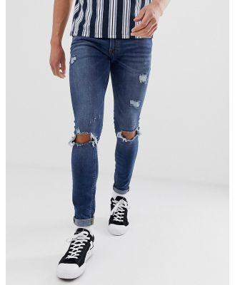 Jack & Jones Intelligence spray on skinny jeans with rip detail in mid blue-Black
